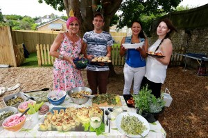Residents celebrating in the new garden with food grown in it